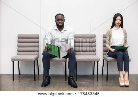 Time for job interview. Young man and woman in office. They sitting, holding CVs and waiting for job interview. Empty chairs. Nice light interior