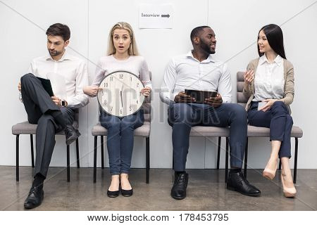 Time for job interview. Young men and women in office. They sitting and waiting for job interview. One woman pointing at clock. Nice light interior