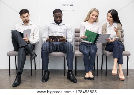Time for job interview. Young men and women in office. They sitting and waiting for job interview. Woman chatting. Nice light interior