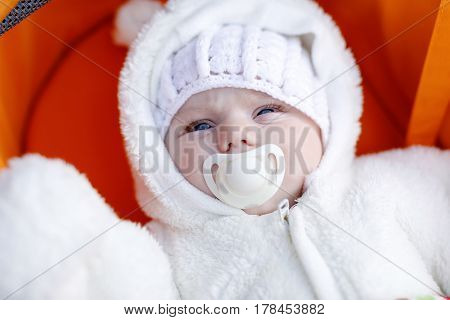 Portrait of newborn baby in warm winter clothes. Beautiful cute girl of 3 months in warm white overall and vintage wool cap. Peaceful child in pram during outdoor walk.