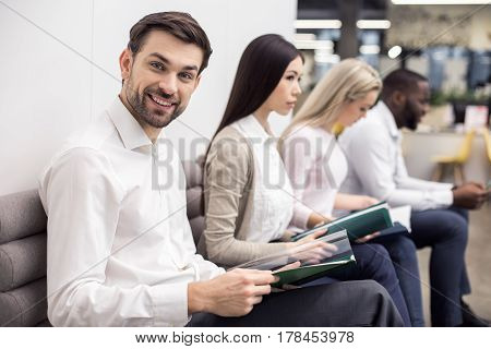 Time for job interview. Young men and women in office. They sitting, holding CVs and waiting for job interview. One man looking at camera and smiling. Nice light interior