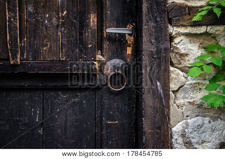 part of old brown wooden door with rusted iron ring