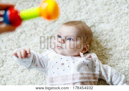 Cute adorable newborn baby playing with colorful rattle toy on white background. New born child, little girl looking hand of mother or father. Family, new life, childhood, beginning concept