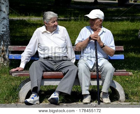 Two old gentlemen siting and talking, on the park bench on a nice, sunny day