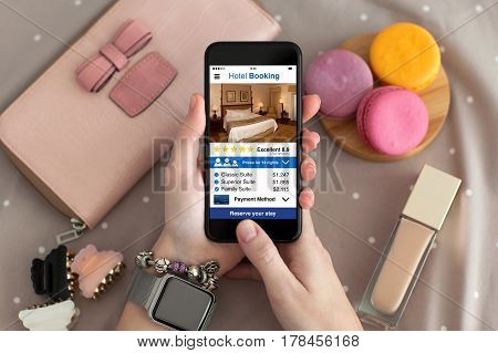 female hand with jewelry and watch holding phone with app hotel booking screen