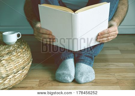 Young man sitting on the wooden floor drinking coffee while reading a book. Empty copy space for Editor's text.
