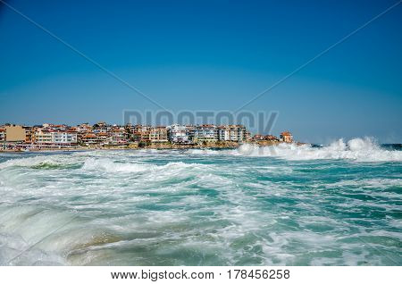seaview with waves and old town on background