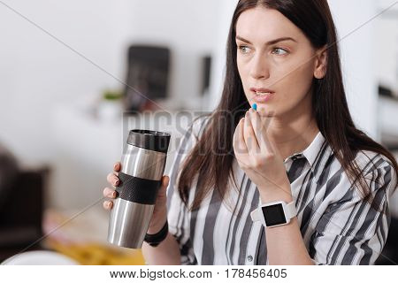 Take vitamin. Photo of pretty office worker keeping her mouth opened having smart watches on left hand, looking sideways