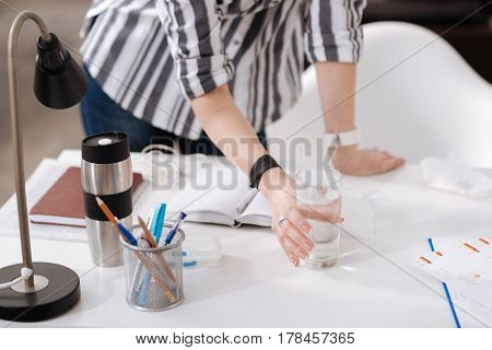 For taking tablets. Close up of woman arms that having bracelet and watches, left hand lying on the table while right one touching glass