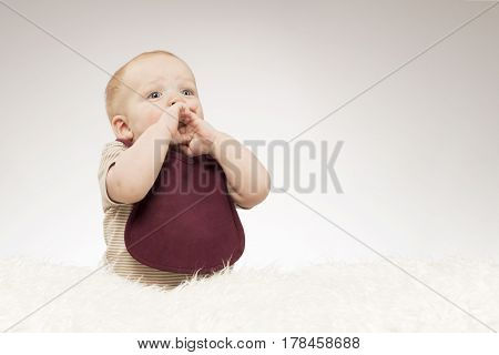 Suprised infant boy sitting on the white blanket. Horizontal studio shot. Copy space