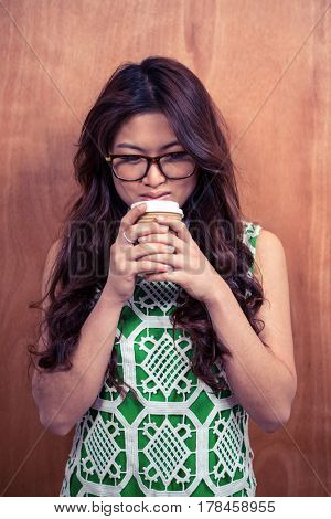 Asian woman wearing eyeglasses holding disposable cup