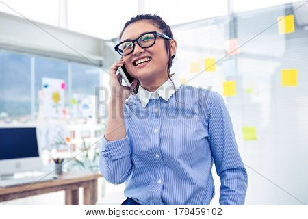 Smiling Asian businesswoman on phone call in office