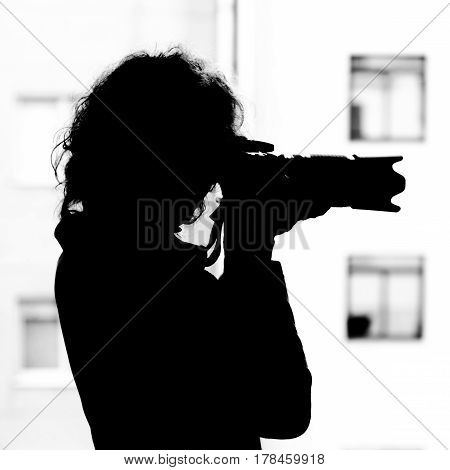 monochrome silhouette of a woman with a SLR camera