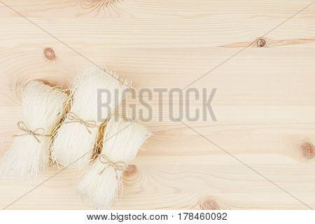 Sheaf raw asian cellophane noodles on beige wooden board with copy space top view.