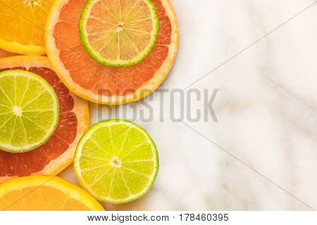 Vibrant juicy citrus fruits on a white marble texture with copy space. Grapefruit, lime, and orange slices