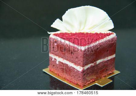 Red velvet cake with fresh raspberry on black background
