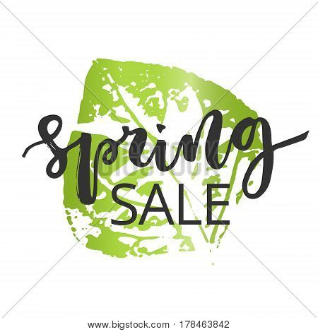 Spring sale hand written inscription with green leaf on white background