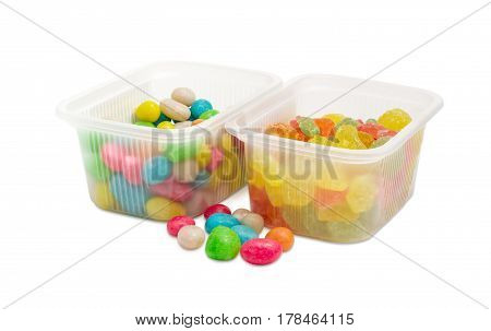 Varicolored sugar candies and candies made of the raisins with hard sugar shells and called sea pebbles in two small plastic containers and several candies separately beside on a light background