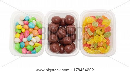 Top view of the malted milk balls covered chocolate varicolored sugar candies and candies made of the sugar glazed raisins in different small plastic containers closeup on a light background