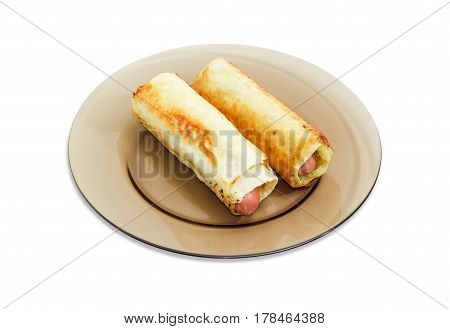 Two cooked sausage rolls made of the Vienna sausages wrapped in puff pastry on dark glass dish on a light background