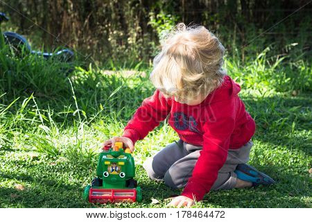 Little boy playing with toy harvester underneath trees outdoors