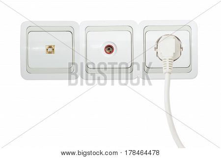 Block of three various white and gray domestic wall sockets including power socket with the connected white power cable telephone socket and TV aerial coaxial socket on a light background