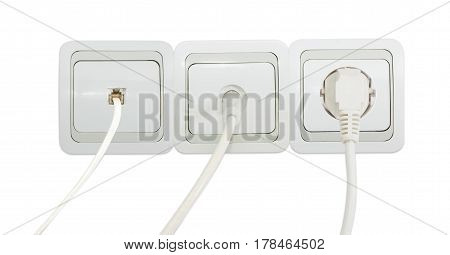 Block of three various white and gray domestic wall sockets including power socket telephone socket and TV aerial coaxial socket with connected corresponding cables on a light background