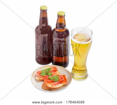 Two different bottles and glass of the lager beer and two sandwiches made with a salted trout on the saucer on a light background