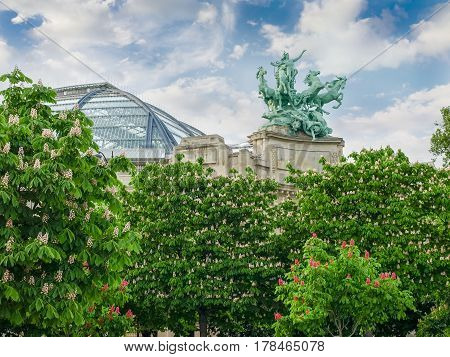 Bronze allegorical statue group over the southern wing of the main facade and part of the glass vaulted roof of the Great Palace built in 1900 with flowering chestnuts in the foreground in Paris