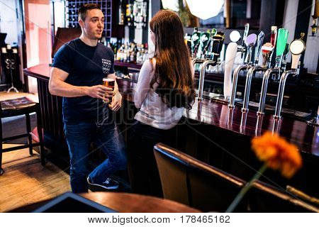 Couple talking and having a drink in a bar