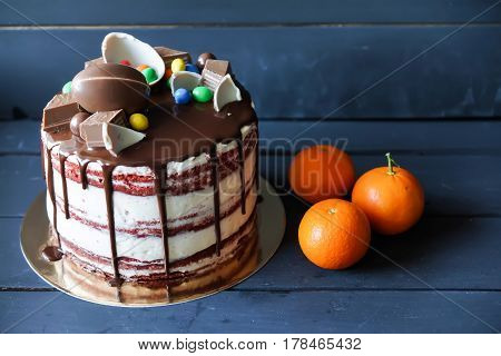 Delicious chocolate cake with dark chocolate sauce and with chocolate candies, tangerines