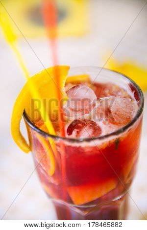Red cocktail with red and yellow straws , orange wedge and ice in high glass