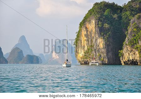 Yacht and catamaran in the sea among the rocky islands.