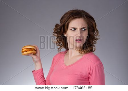 young beautiful girl disdainfully holding a junk food from fast food sandwich and do not want to eat on a gray background