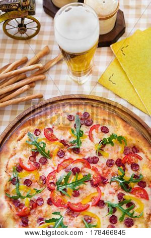 Tasty pizza with cheese, tomato and meat, with glass of beer on served table with plaid tablecloth