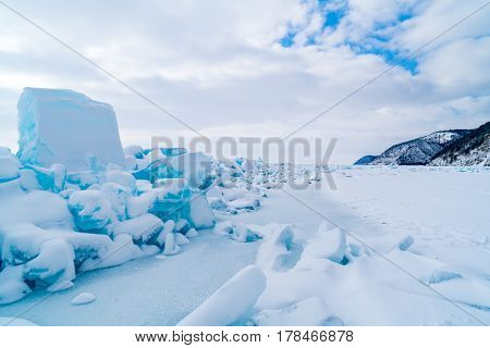Row of ice blocks and the mountain covering with snow at lake Baikal in Russia in the winter