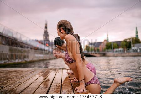Side view of young people on the edge of the pier at lake. Woman with friends enjoying at the lake.