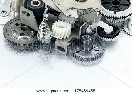 Various Cogwheels And Other Parts Of Industrial Machinery On Scratched Background