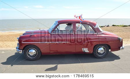 FELIXSTOWE, SUFFOLK, ENGLAND - MAY 01, 2016: Classic Red Vauxhall Velox Motor  being driven  on seafront promenade.