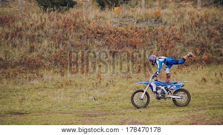 MX moto woman Biker shows acrobatic at cross racing - rider on a dirt motorcycle, telephoto