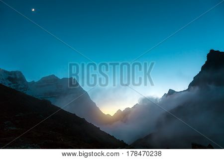 Evening high Altitude Mountain Range View with Sunset between Rocks and Moon rising