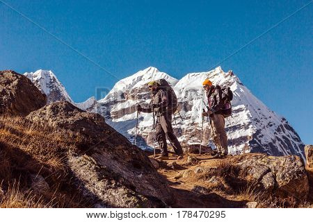 Two adult Mountain Climbers with Backpacks Gear and high Altitude Clothing walking on rocky Ridge with Himalaya Summits on Background