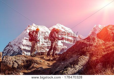 Two adult Mountain Climbers with Backpacks Gear and high Altitude Clothing walking on rocky Ridge with Himalaya Summits and shining Sun on Background