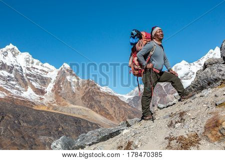 Mature high Altitude Himalaya Nepalese Mountain Guide staying on rocky Slope with Backpack Climbing Gear and looking Up poster