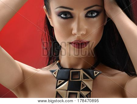 Fierce lady. Gorgeous hot and sexy young brunette with professional makeup posing seductively on red background touching her hair beauty cosmetics fashion style concept