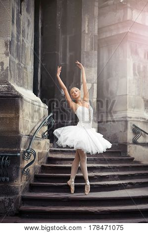 She can teach you grace. Vertical soft focus portrait of a stunning ballet dancer woman performing on the stairway of an old castle
