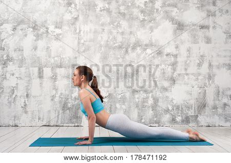 Side view of young woman practicing yoga indoors. Fit girl wearing sportswear doing Cobra Pose.