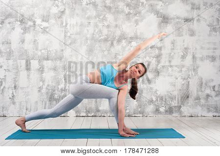 Fit caucasian woman practicing yoga indoors. Beautiful girl exercising on blue mat against grey wall.