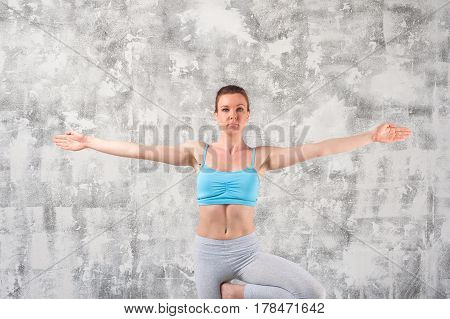 Young caucasian woman practicing yoga indoors. Fit girl standing on Tree Pose.