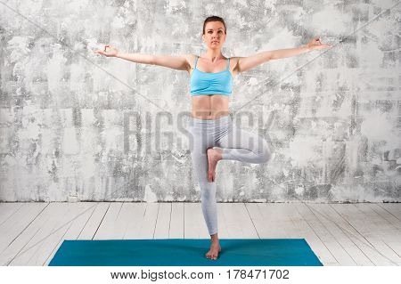 Young attractive woman wearing sportswear staying in Yoga Tree Pose. Fit girl exercising on blue mat against grey wall.